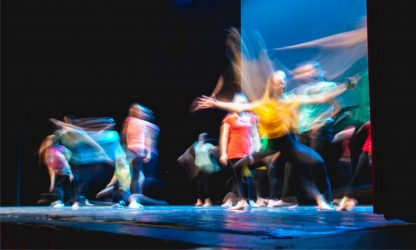Group of dancer in colored clothes dancing on the stage in long